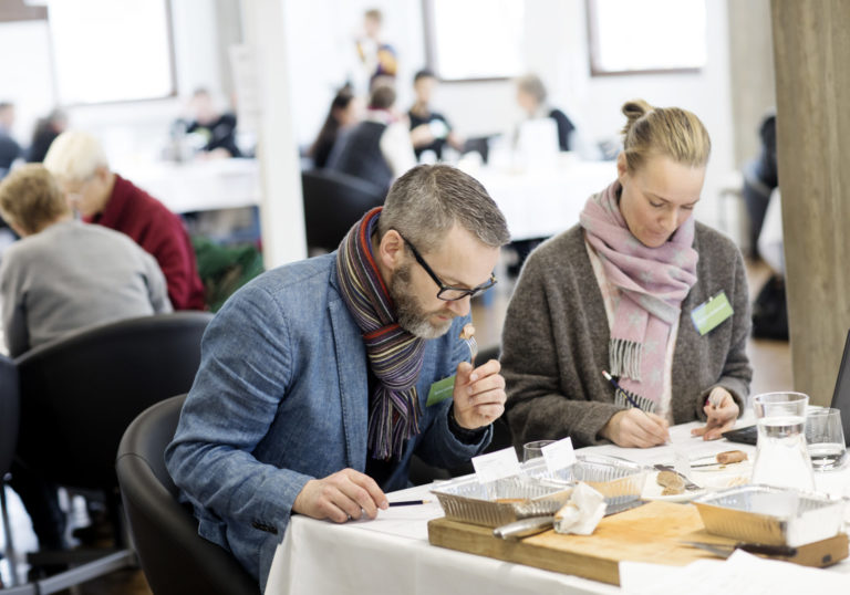 Man och kvinna provar mathantverk, jury i tävling